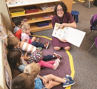 Claire Gill reads a book to her kindergarten students.