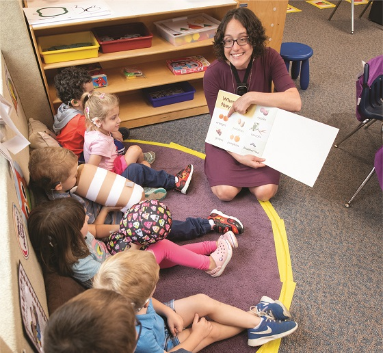 Claire Gill reads a book to her kindergarten students